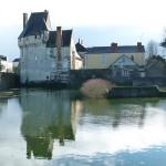 Vue du château et de ses douves inondées en venant d'Angers